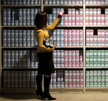 (Photo - woman scanning shelf of canned data)