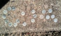 (Photo - pennies embedded in the sidewalk)
