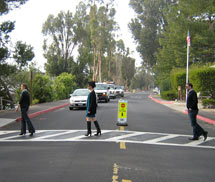 (Photo - cars stopped for pedestrians at a crosswalk)